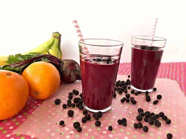dark purple blueberry immune boosting smoothie with striped straw sitting next to a bunch of fruit