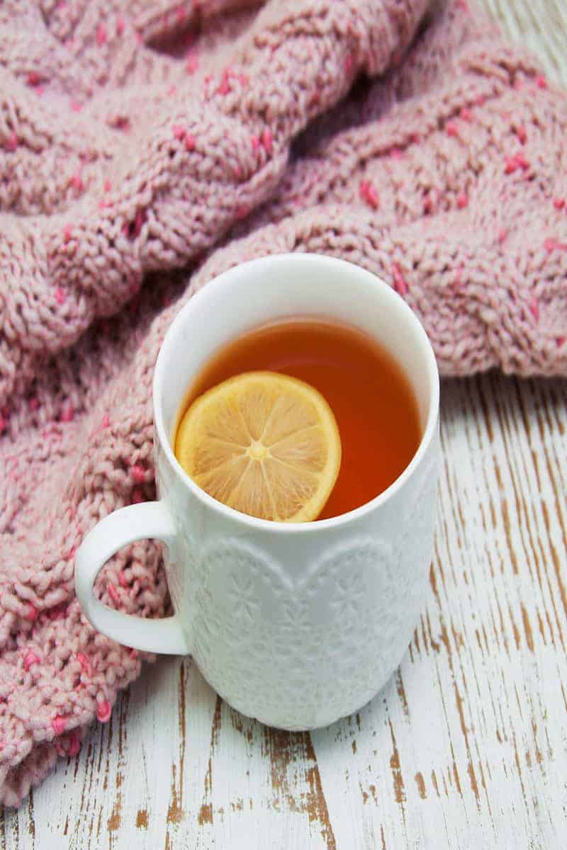 Cup of tea with lemon in white cup next to pink knit blanket