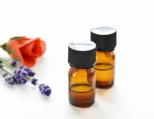 two amber glass essential oil bottles next to lavender and rose