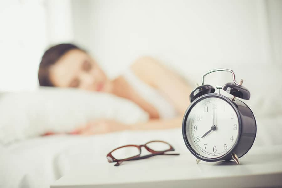 woman sleeping in bed next to black alarm clock