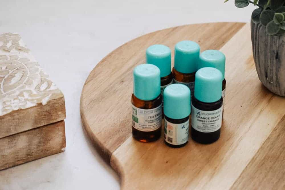 Florihana Essential Oils sitting on cutting board next to plant for Florihana essential oils review