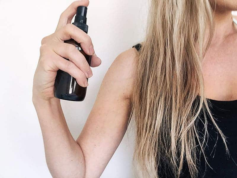 woman spraying diy sea salt hair spray in hair