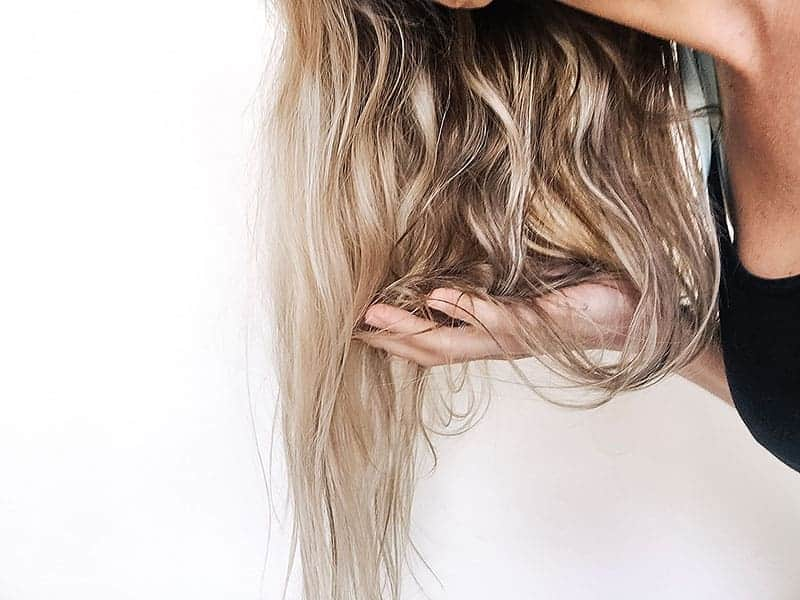 Woman scrunching diy sea salt hair spray into hair