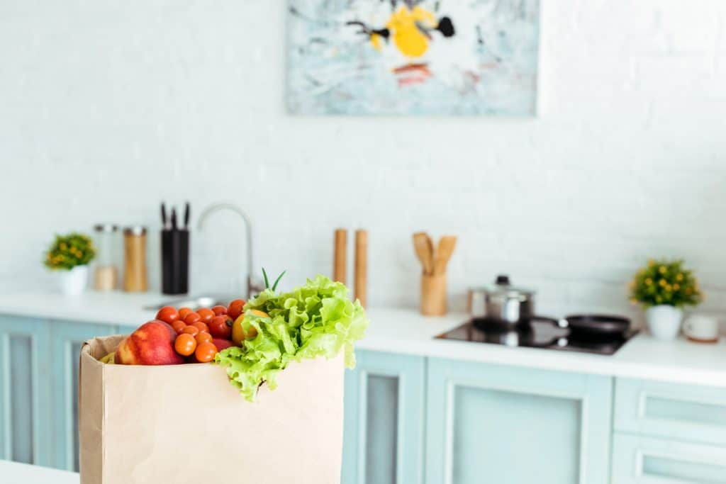 Fruits and vegetables in a brown grocery bag sitting on kitchen counter