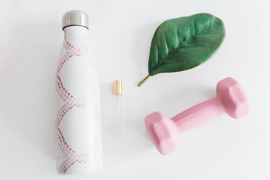 Water bottle next to leaf next to essential oil roller bottle next to pink dumbbell on whitebackground