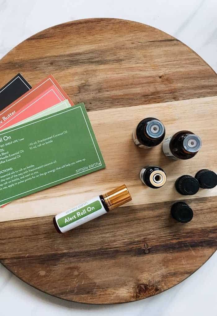 Items from essential oil subscription box laying on wooden cutting board next to essential oil bottles