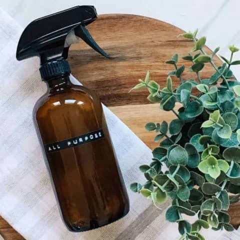 Homemade all purpose cleaner in glass amber spray bottle on wooden cutting board
