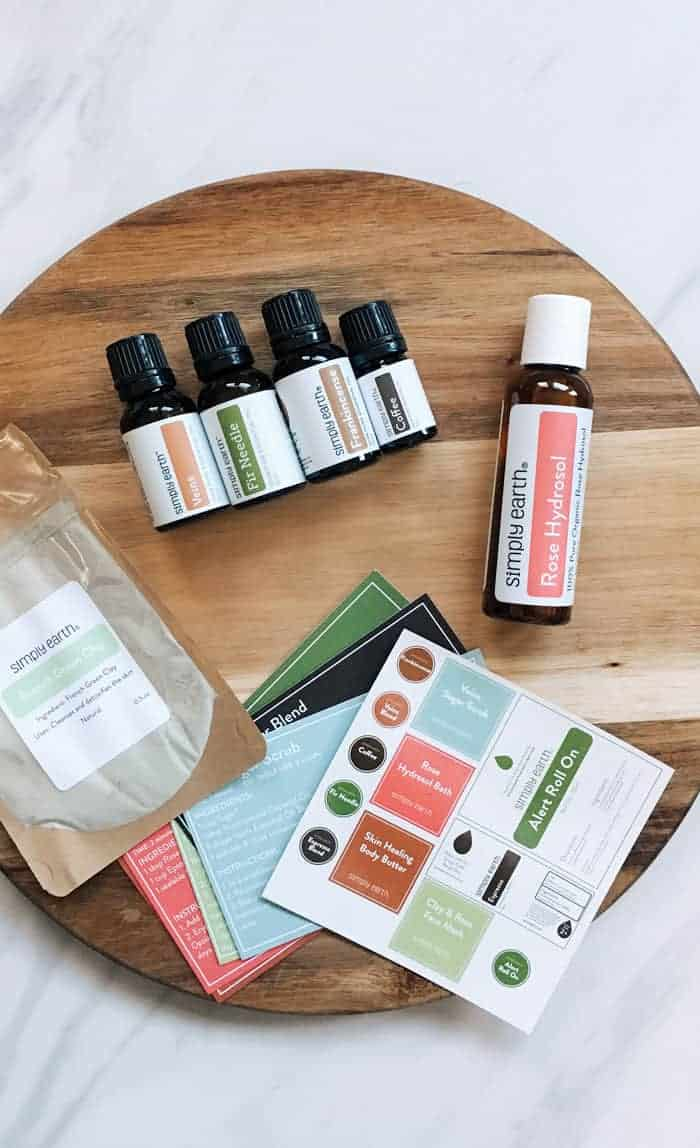Items from essential oil subscription laying on wooden cutting board