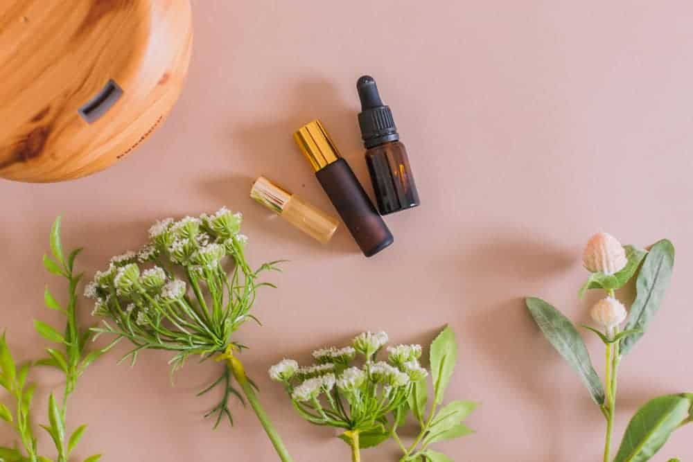 Essential oils for hormone health lying on pink surface next to wild flowers and essential oil diffuser.