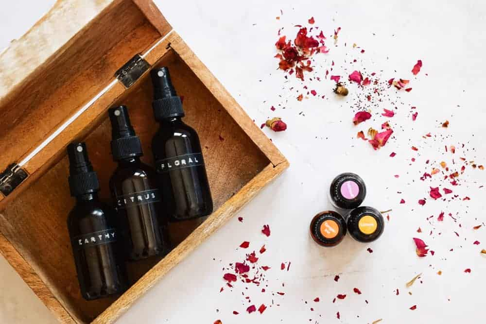 photo of diy body spray lying in a wooden box next to essential oils