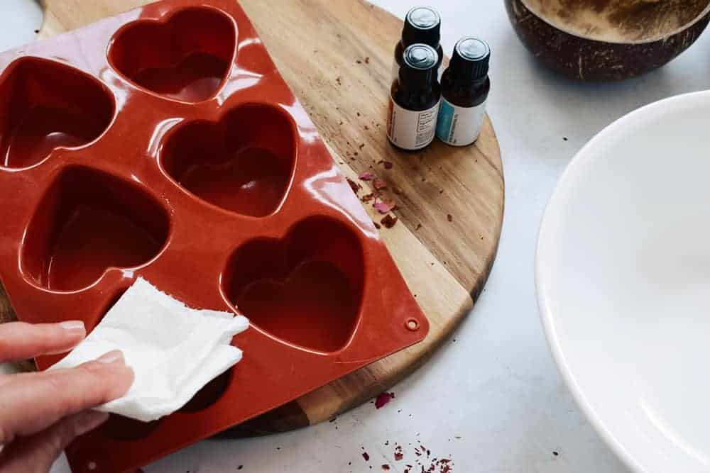wiping inside of heart shaped mold with napkin covered in coconut oil