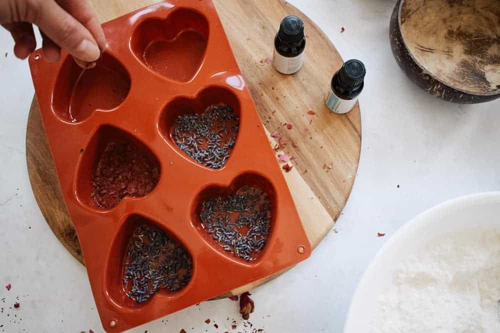 sprinkling dry flowers into bottom of heart shaped bath bomb molds