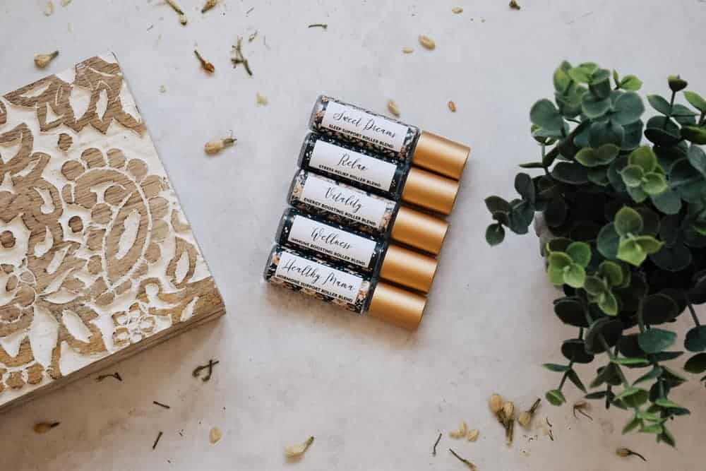 photo of essential oil roller blends for moms sitting next to wooden box and fake plant