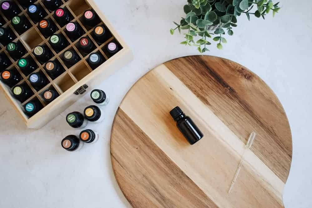 Homemade Thieves essential oil lying on cutting board next to essential oils