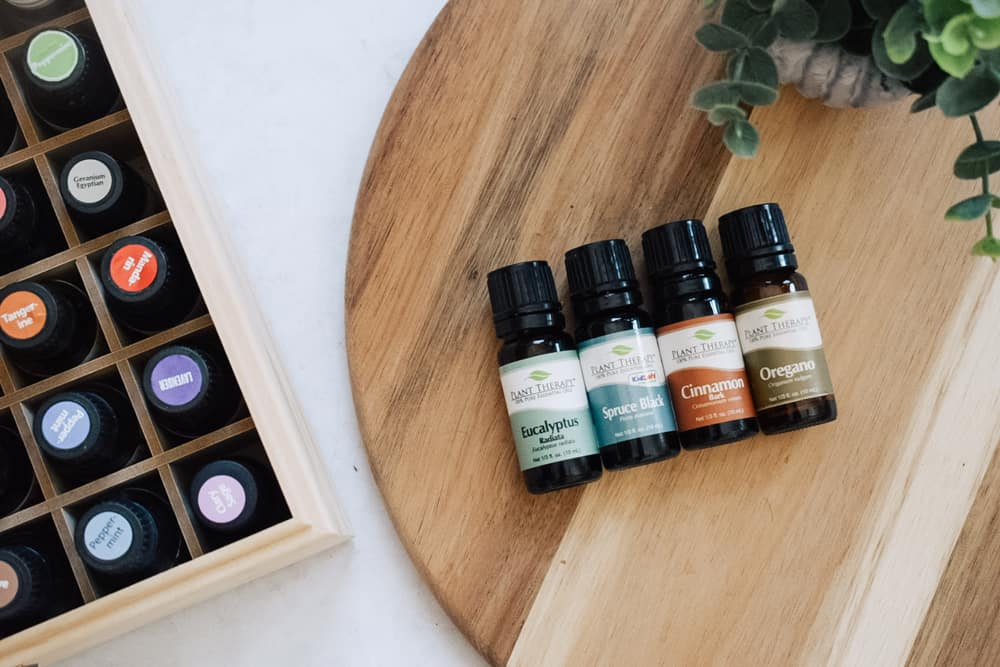 Plant Therapy essential oils on cutting board next to faux plant