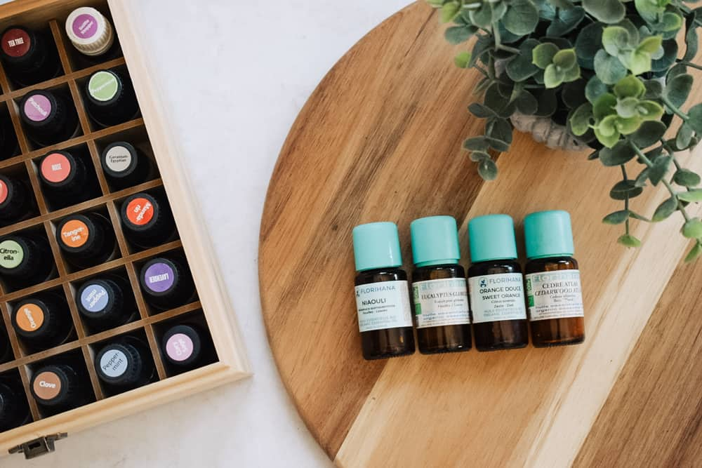 Florihana essential oils on cutting board next to faux plant