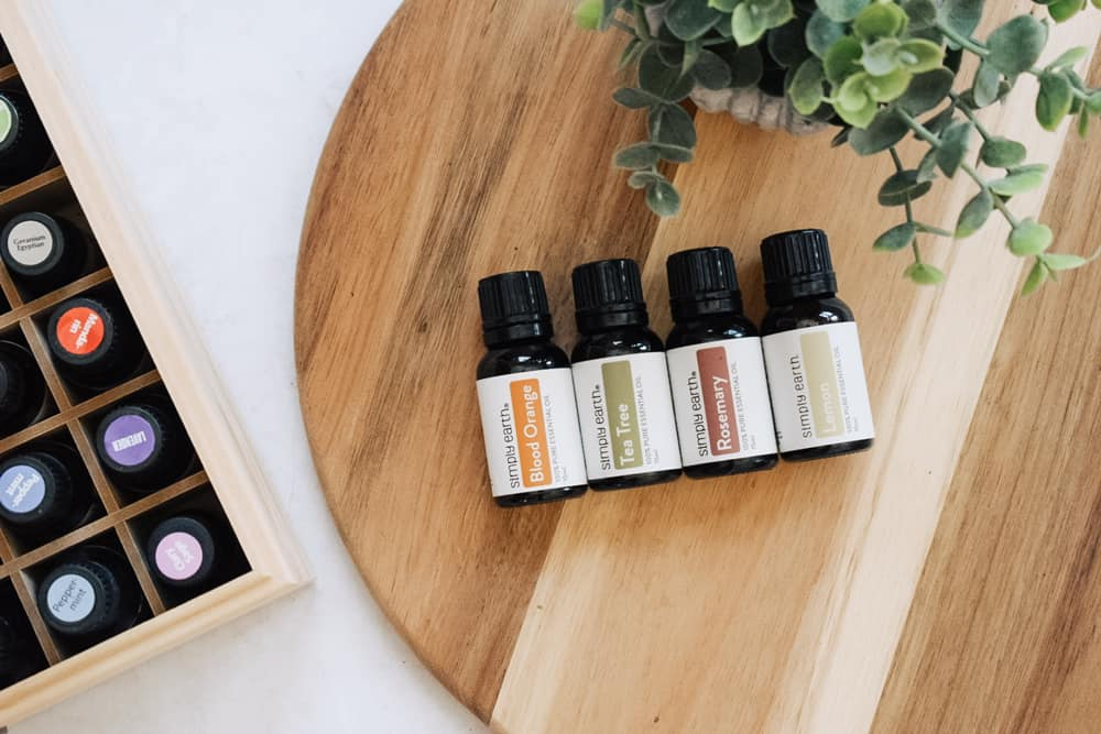 Simply Earth essential oils on cutting board next to faux plant