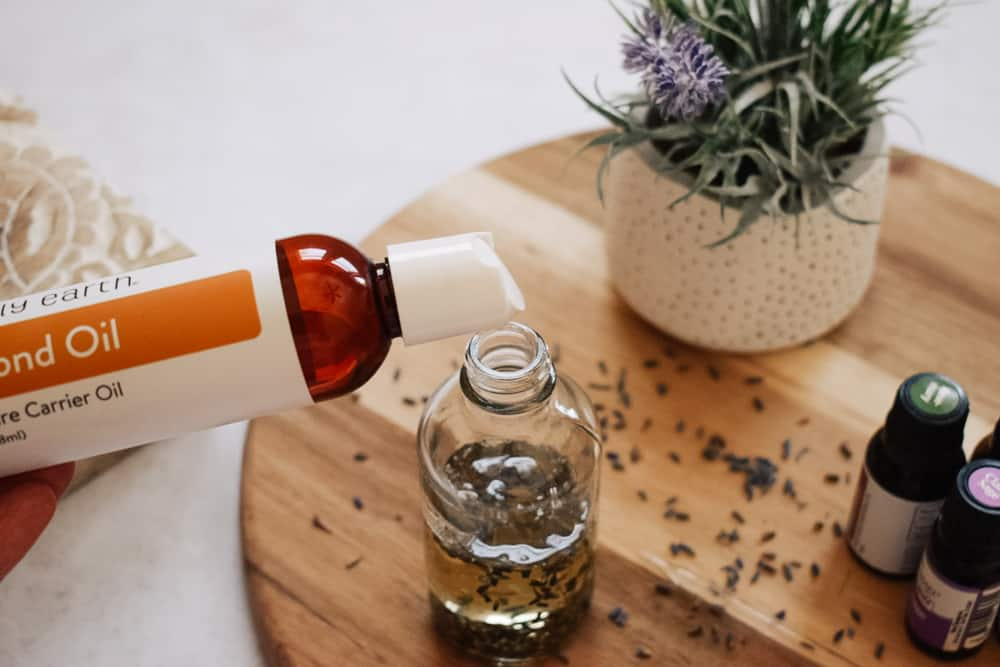 person pouring almond oil into clear glass bottle