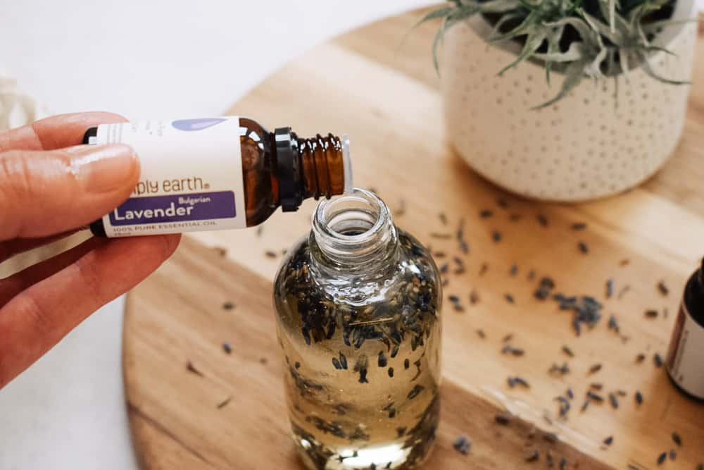person pouring lavender oil into clear glass bottle