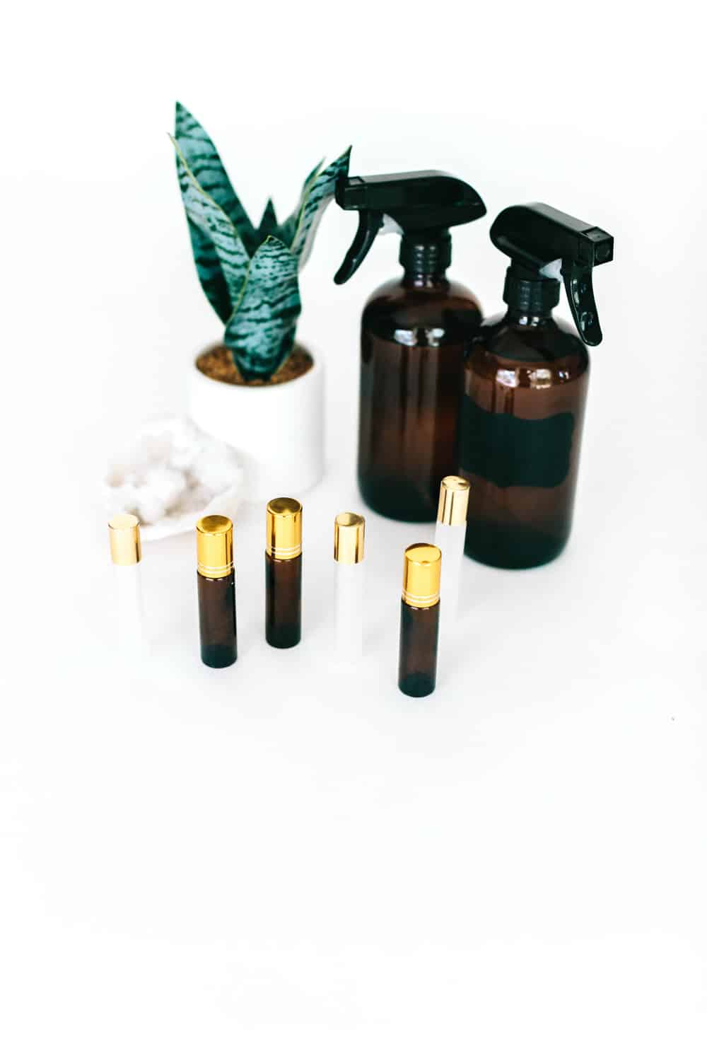 essential oil roller bottles and brown glass spray bottles next to snake plant