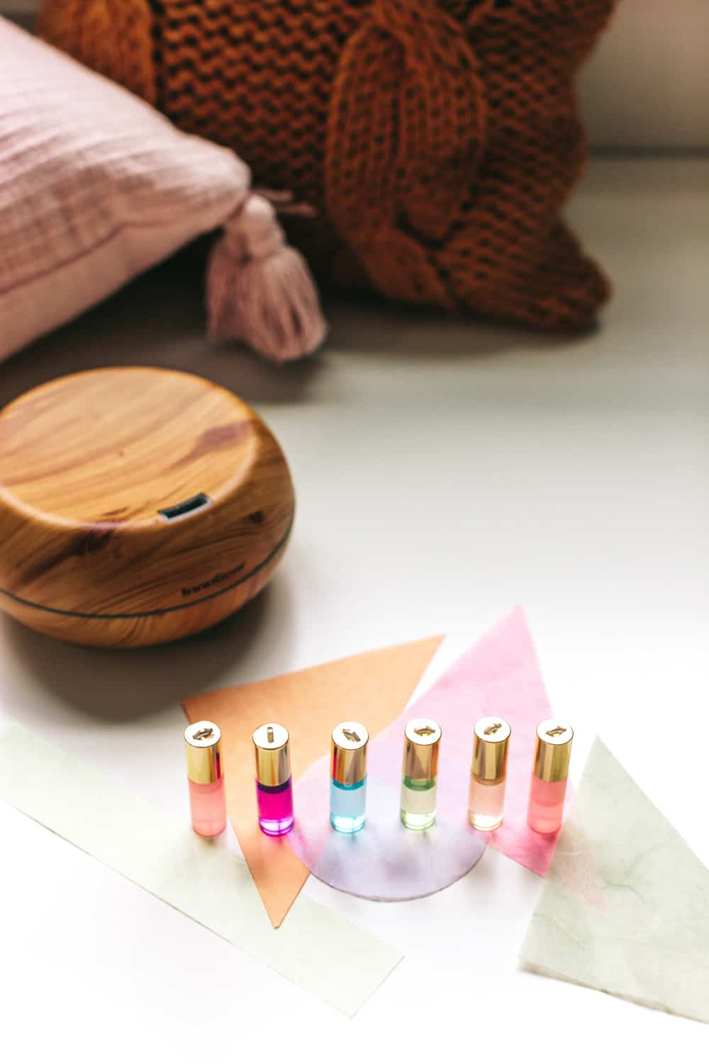 colorful essential oil roller bottles next to essential oil diffuser