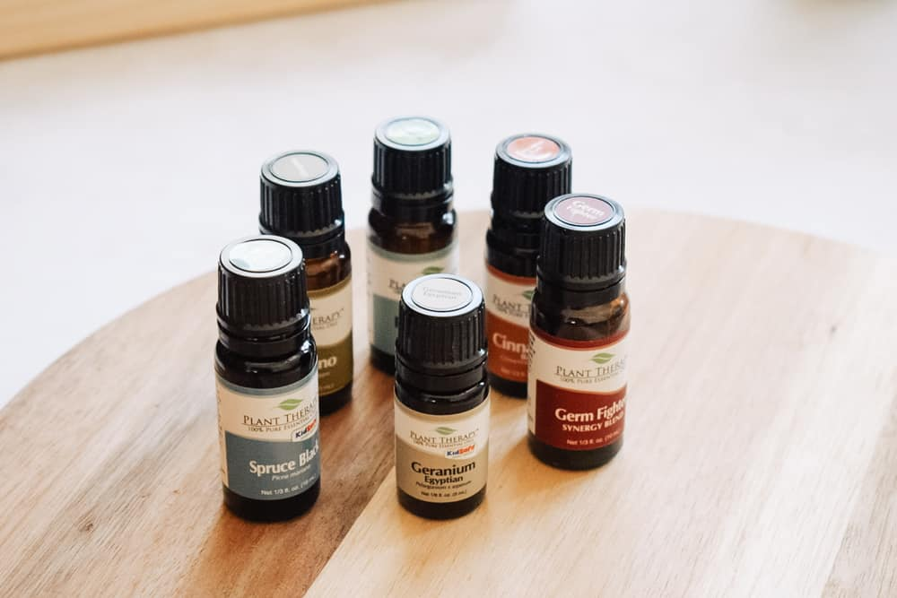 Plant therapy essential oils sitting on a wooden surface.