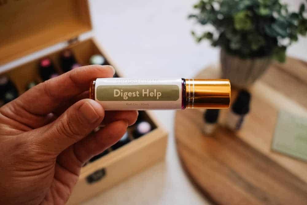 woman holding Simply Earth digest help essential oil roll-on