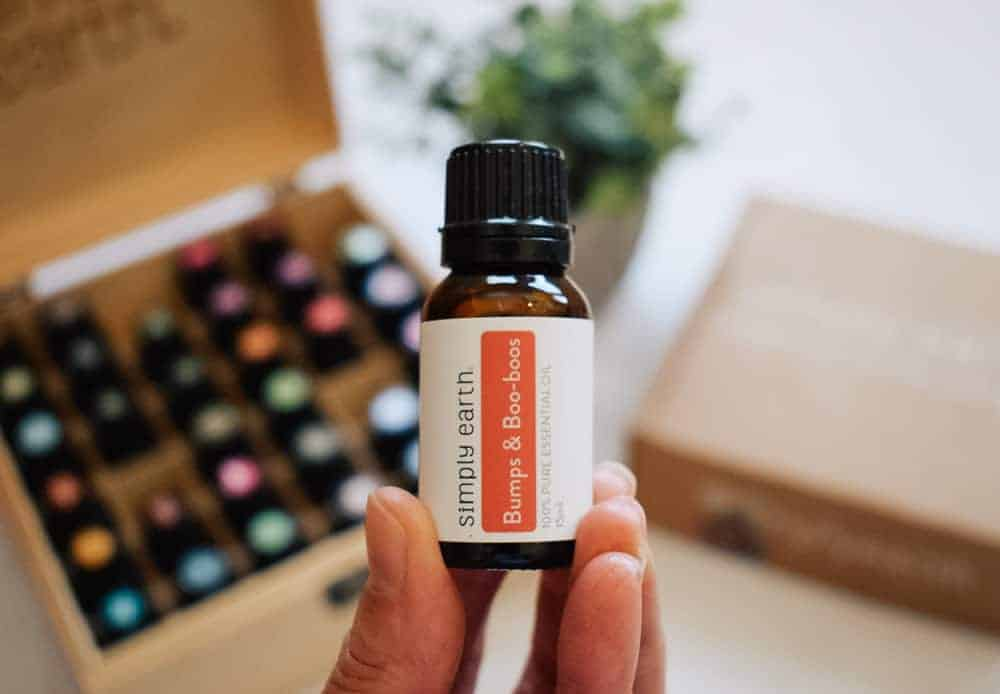 woman holding Simply Earth bumbs & boo-boos essential oil