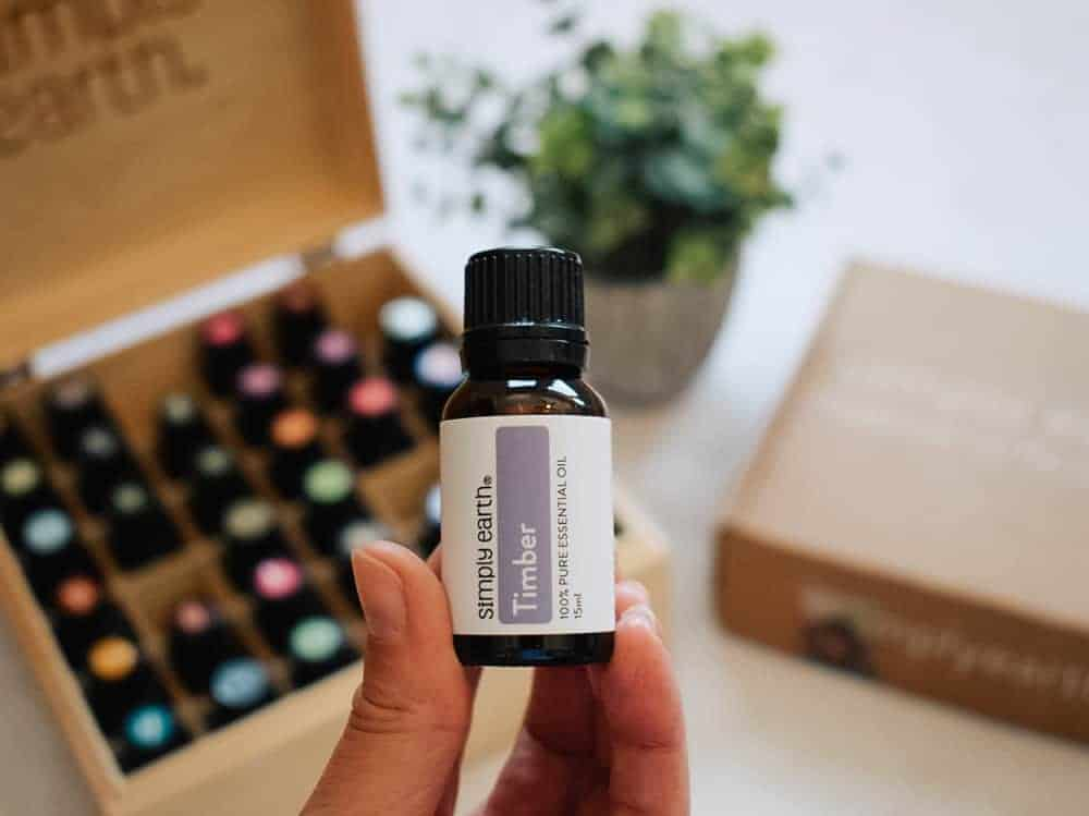 woman holding Simply Earth timber essential oil