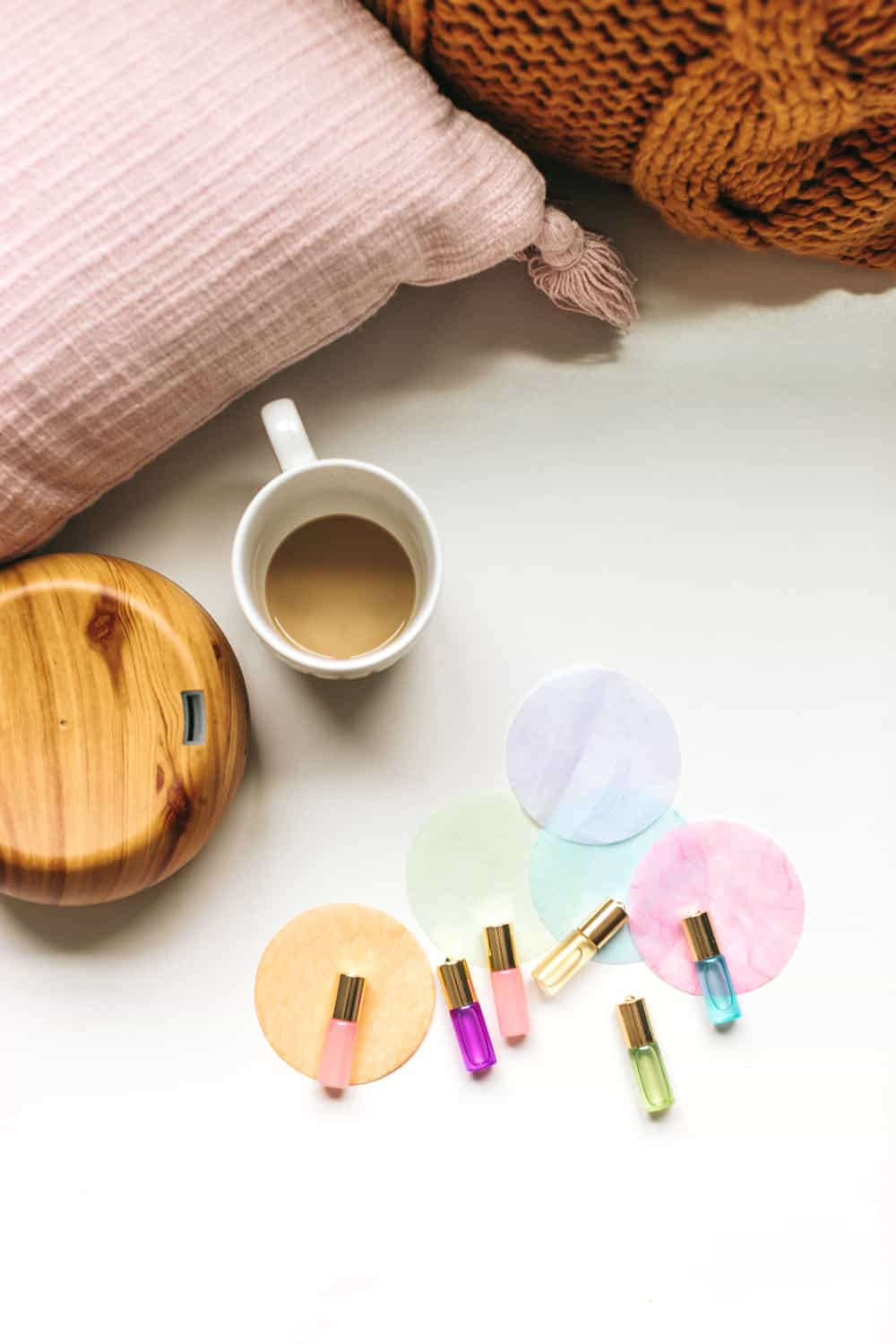 colorful essential oil roller bottles next to coffee cup and pillows