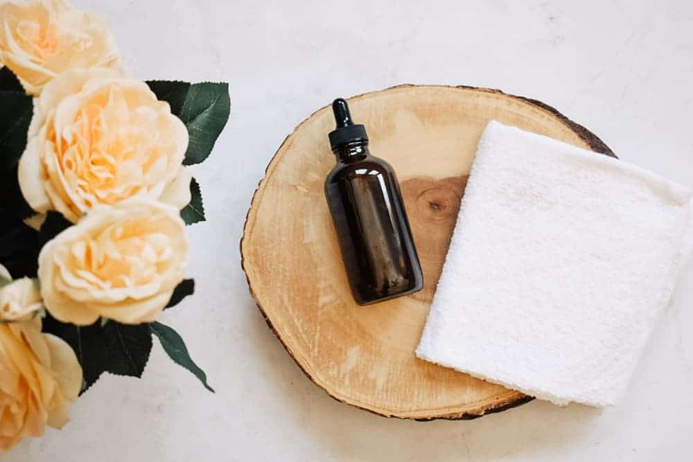Bottle of oil cleanser lying on wood next to white washcloth