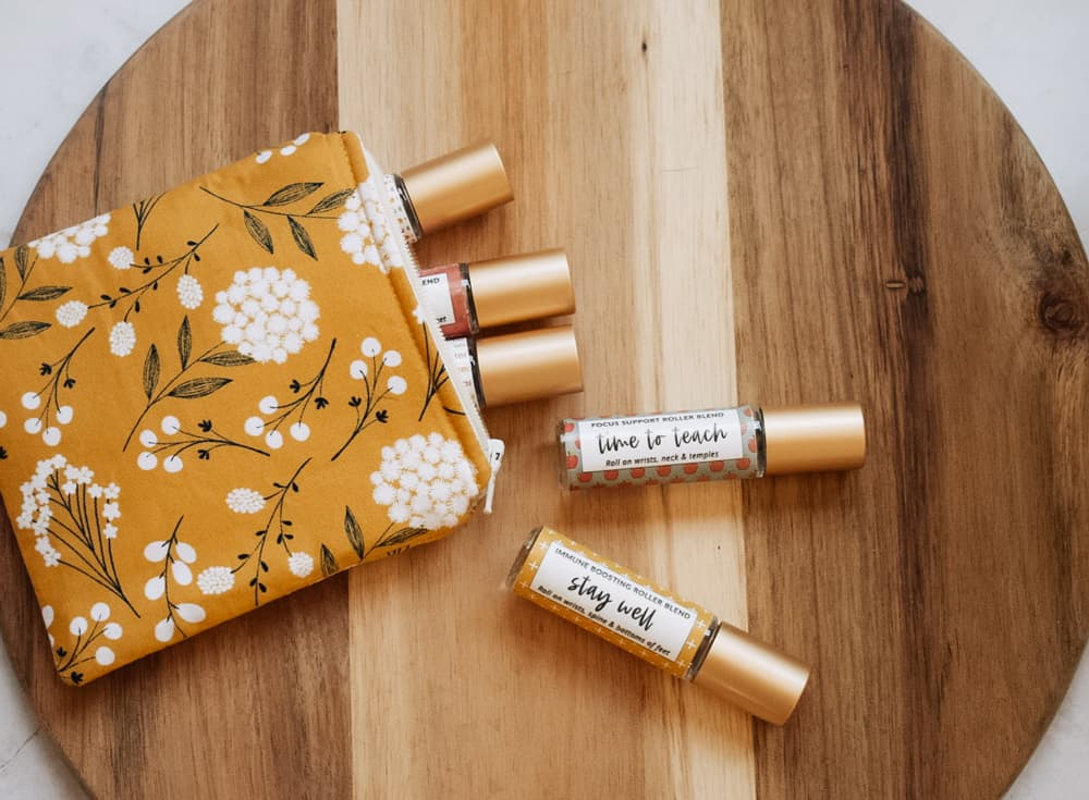 Essential oil roller blends for teachers lying on cutting board next to essential oil bag