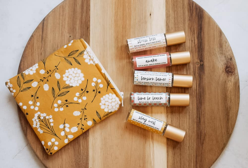 photo of roller blends for teachers layed out on wooden cutting board next to yellow floral essential oil bag