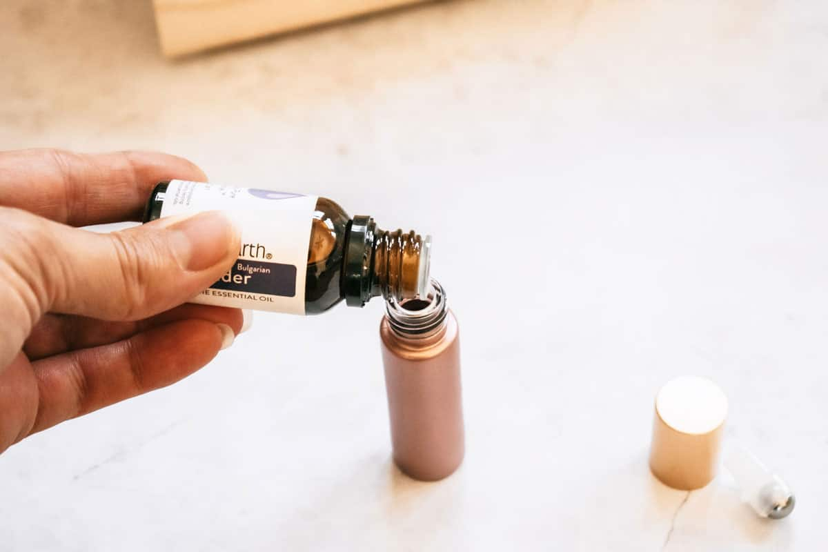 person pouring lavender into roller bottle