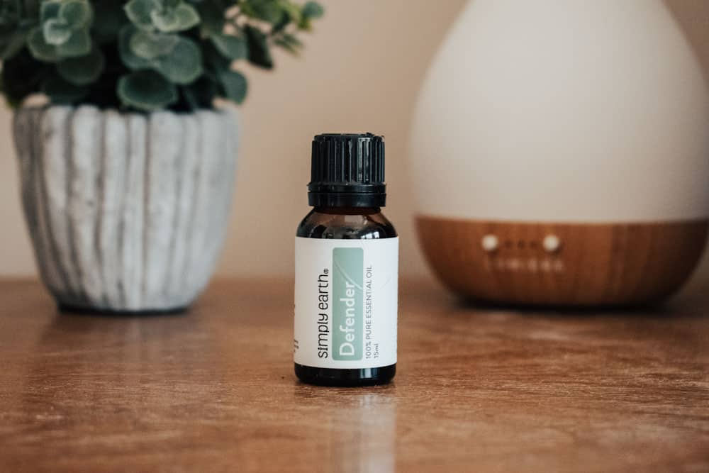 Simply Earth defender essential oil standing next to essential oil diffuser and small plant
