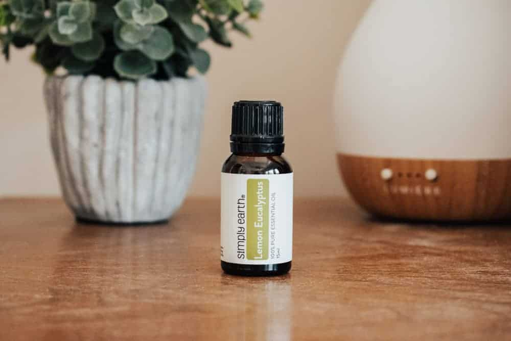Simply Earth lemon eucalyptus essential oil standing next to essential oil diffuser and small plant