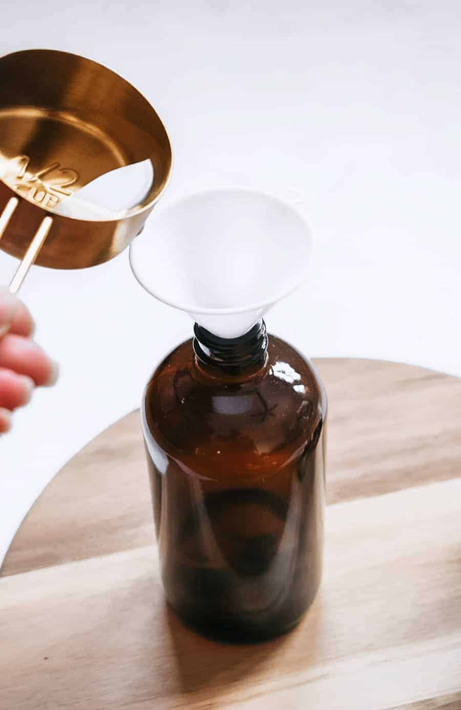 person pouring vinegar into brown glass bottle