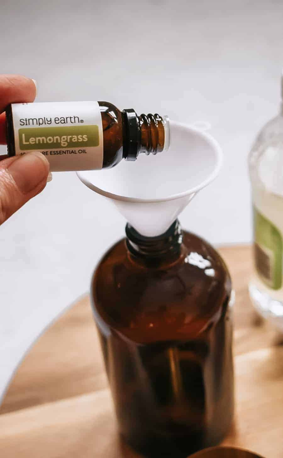 Person pouring lemongrass essential oil into brown glass bottle