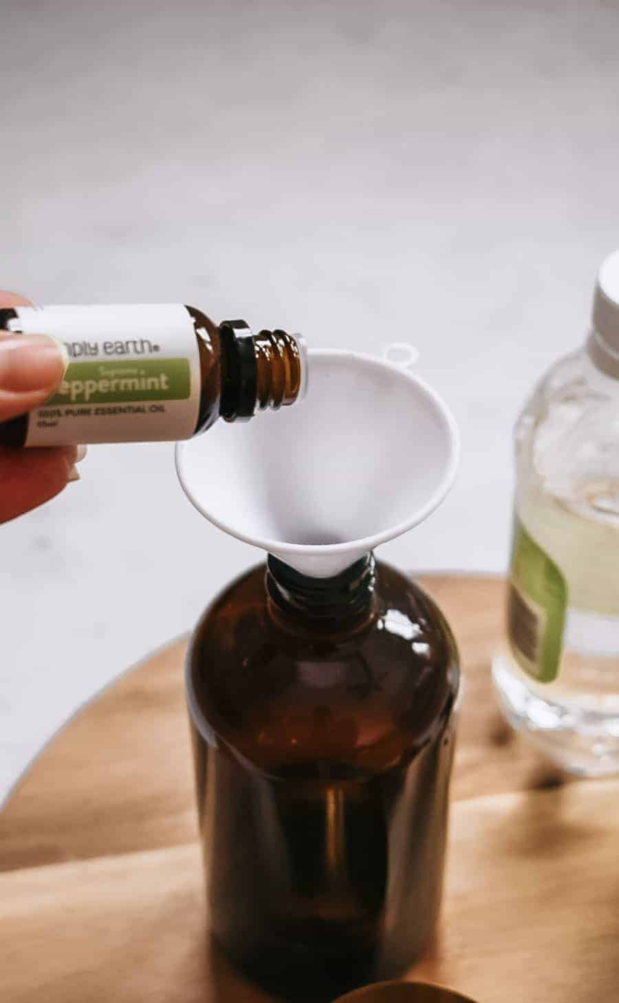 Person pouring peppermint essential oil into brown glass bottle