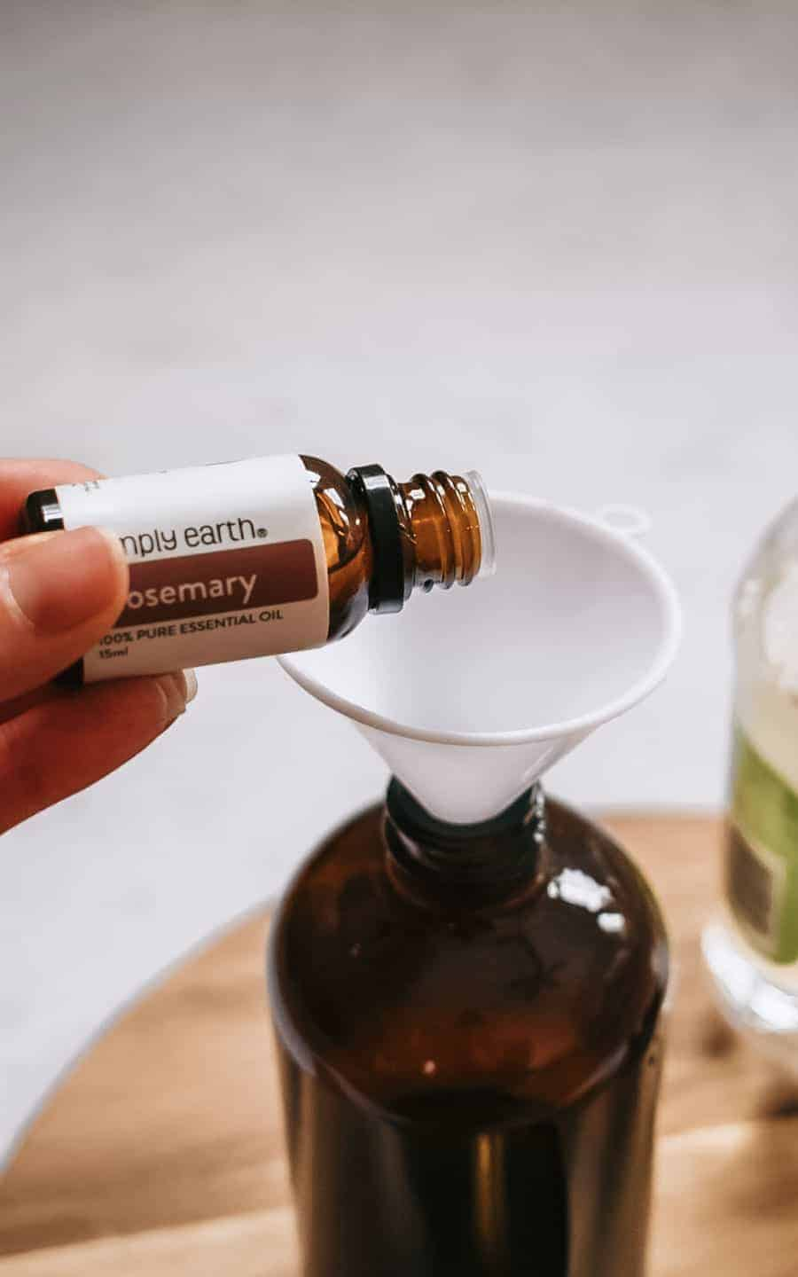Person pouring rosemary essential oil into brown glass bottle