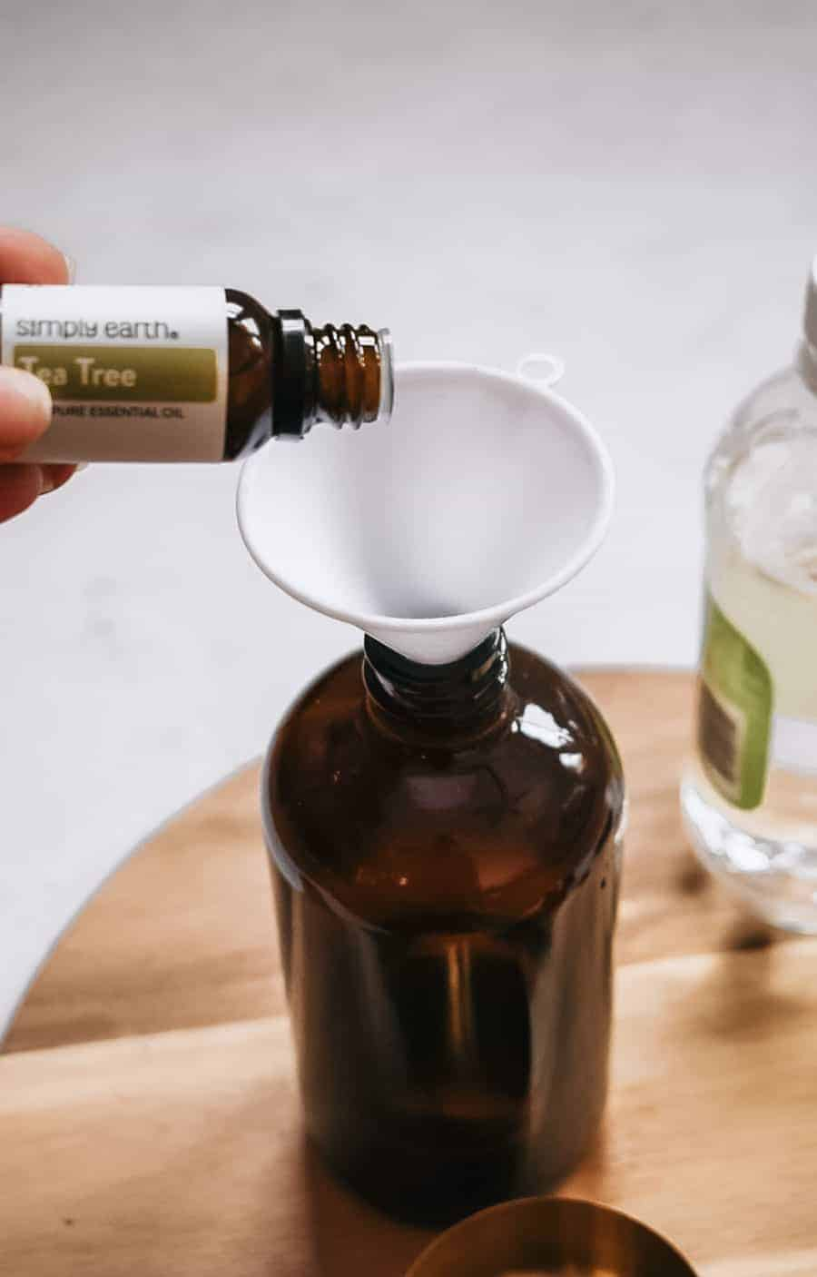 Person pouring tea tree essential oil into brown glass bottle