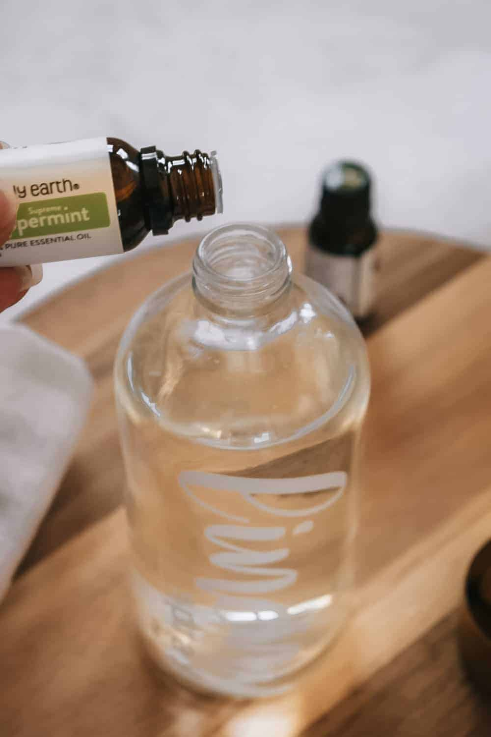 person pouring peppermint essential oil into glass spray bottle