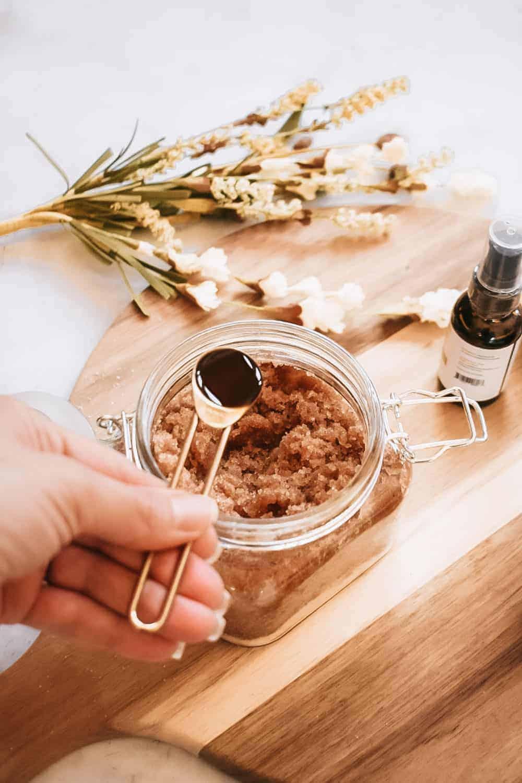 someone adding vanilla extract to diy pumpkin spice body scrub on round cutting board next to fall foliage and fake pumpkin