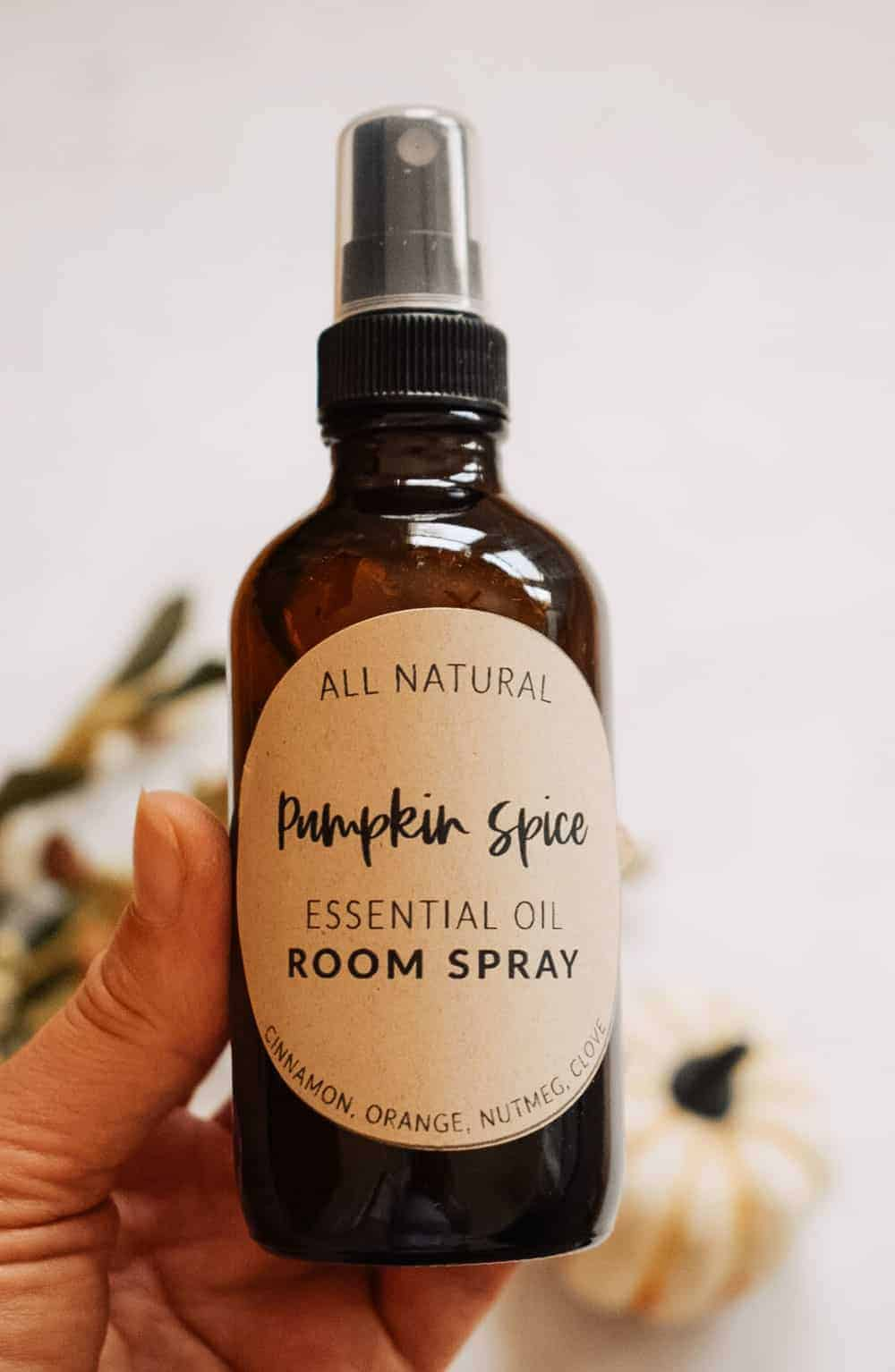 person holding fall room spray so house will smell like fall