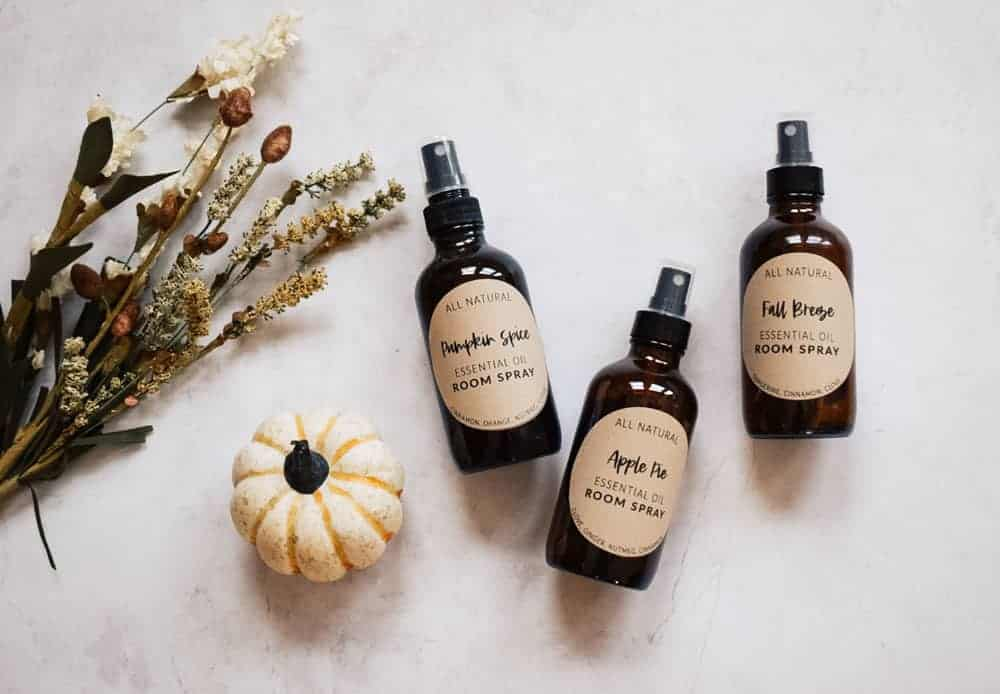 Essential oil fall room sprays lying o white background next to flowers