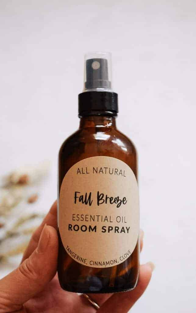 person holding fall breeze fall room spray