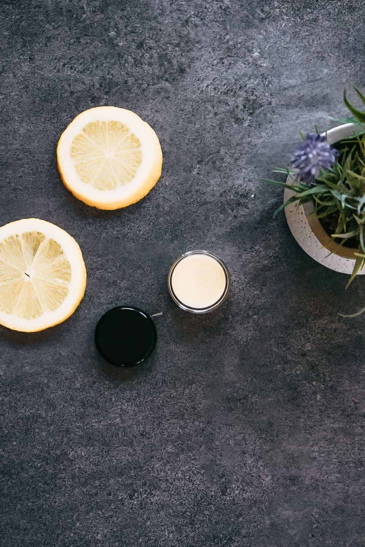 Homemade lemon cuticle cream sitting next to sliced lemons and lavender plant