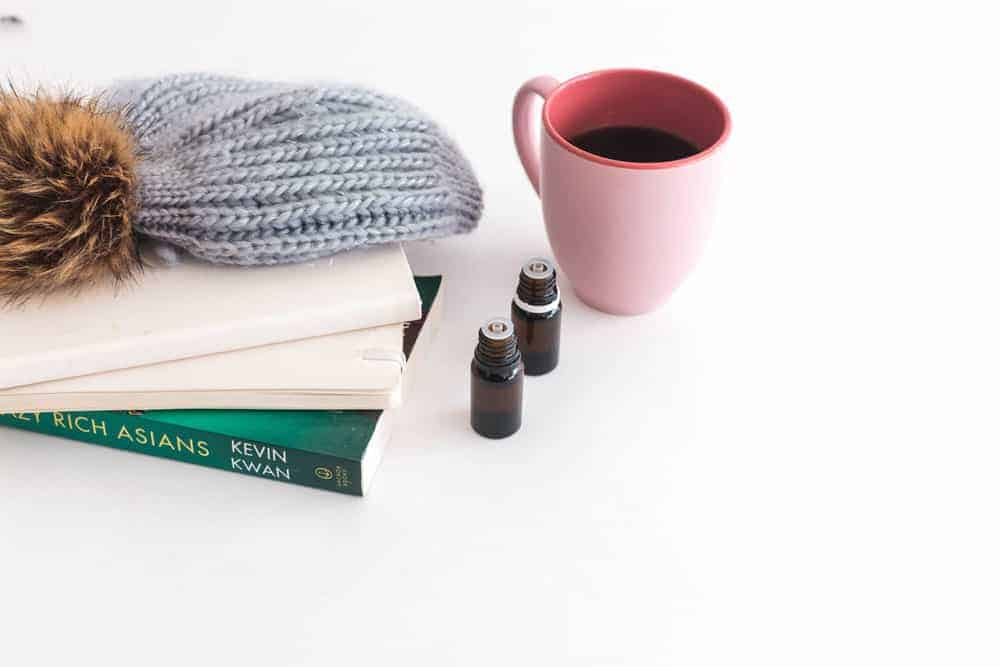 essential oil bottles without caps sitting next to coffee mug, books, and winter beanie