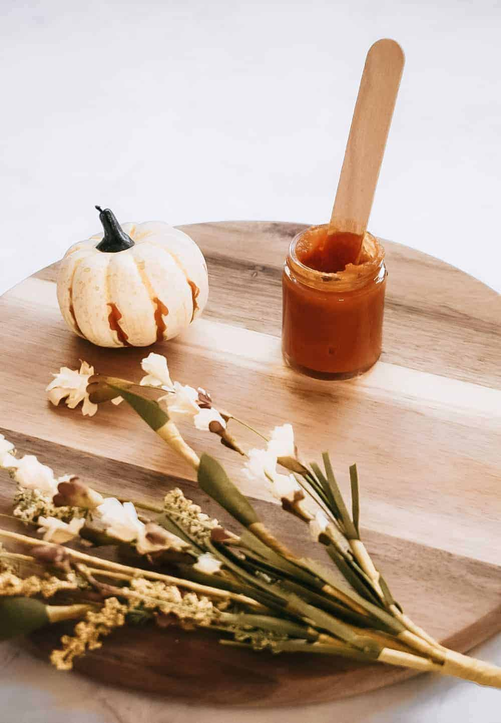 DIY pumpkin enzyme face mask sitting on cutting board next to pumpkin and fall foliage