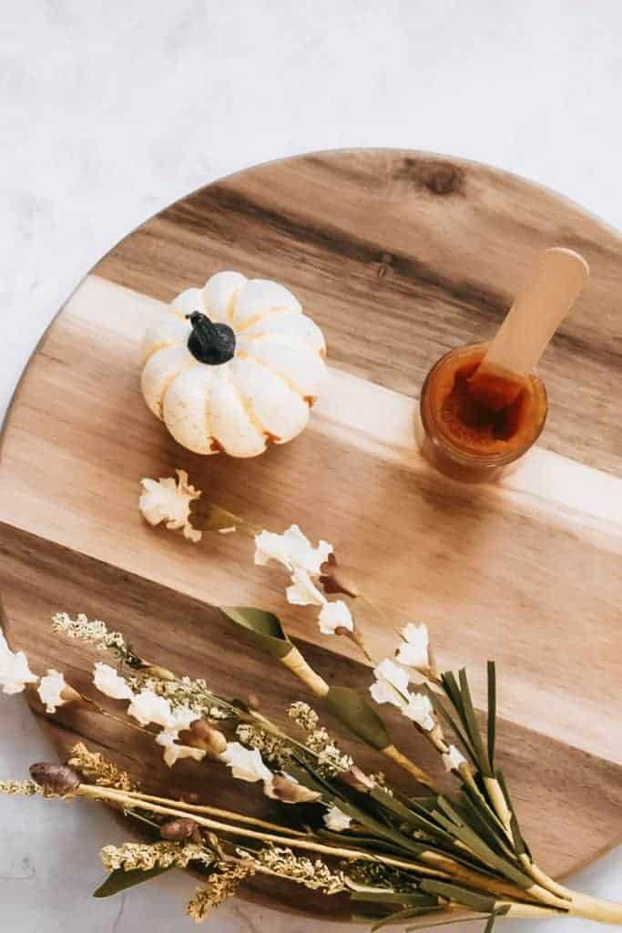 DIY pumpkin enzyme face mask sitting on cutting board next to pumpkin and fall foliage.